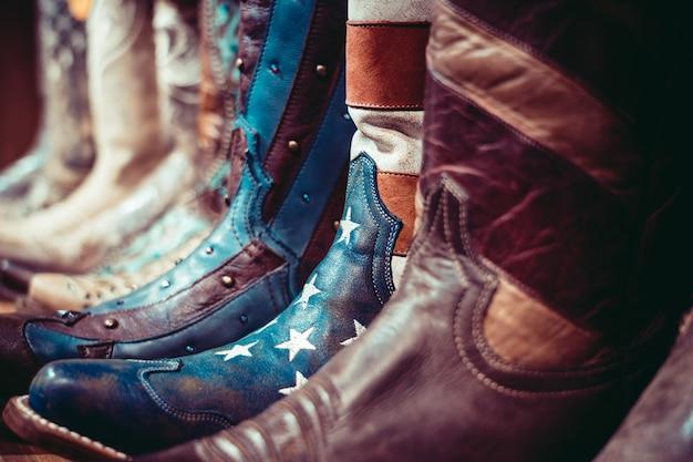 Botas de cowboys em uma prateleira em uma loja com bandeira dos eua