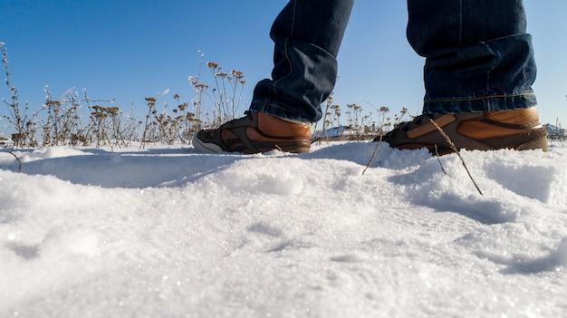 Botas de inverno dos homens na neve. closeup de botas de inverno quente de homens marrons