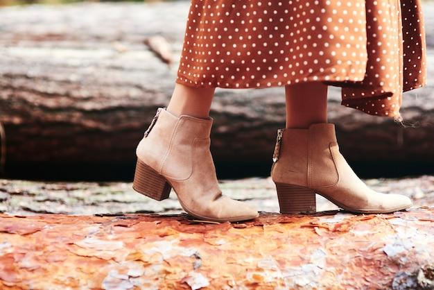 Botas de mulher na floresta outonal