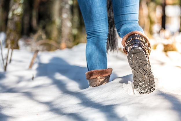 Botas de mulher retrato em uma estrada com neve no inverno andando