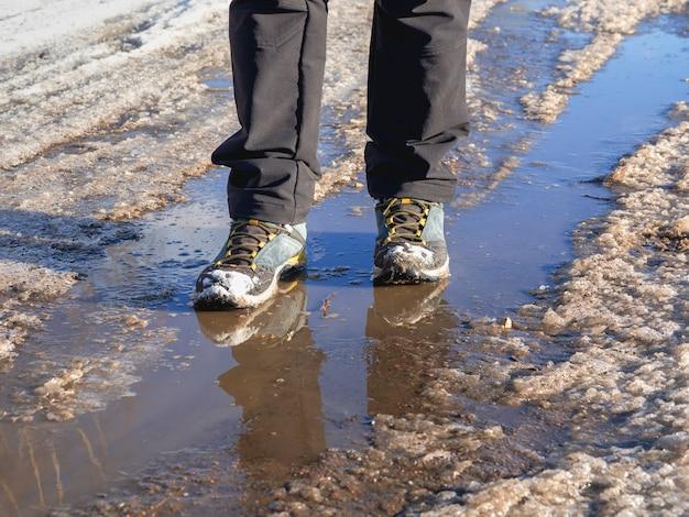 Botas de trekking na primavera lamacenta. o gelo derrete na primavera, um homem atravessa poças d'água na rua, clima de primavera.