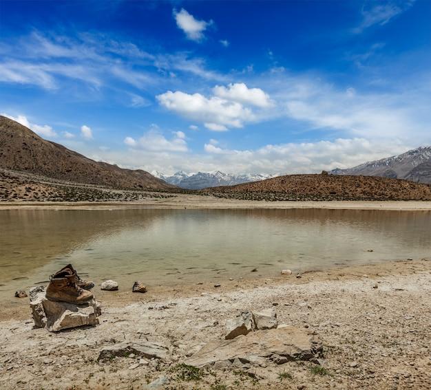 Botas de trekking no lago de montanha no himalaia