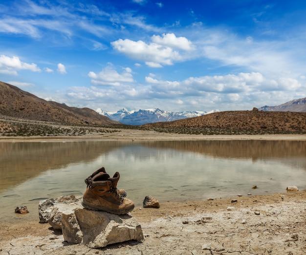 Botas de trekking no lago de montanha no himalaia Foto Premium