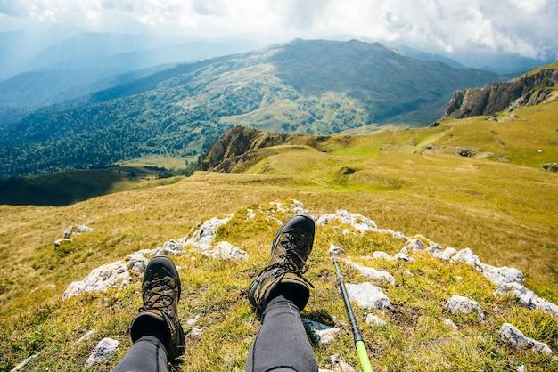 Botas de trekking tendo como pano de fundo uma bela paisagem.