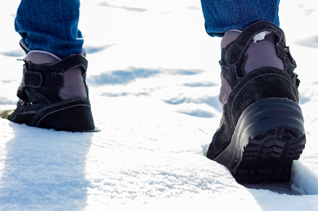 Botas de um alpinista em um cume nevado. conceito de superação, inspiração, expedição e esporte de risco. fotografia de arquivo.