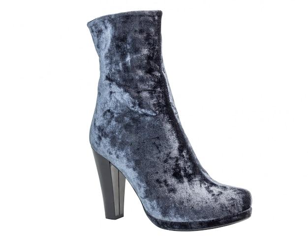 Botas de uma mulher de camurça cinza nos saltos de pé no fundo branco