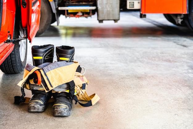 Botas e calças de bombeiro retardador de chama prontas para serem usadas em caso de emergência.