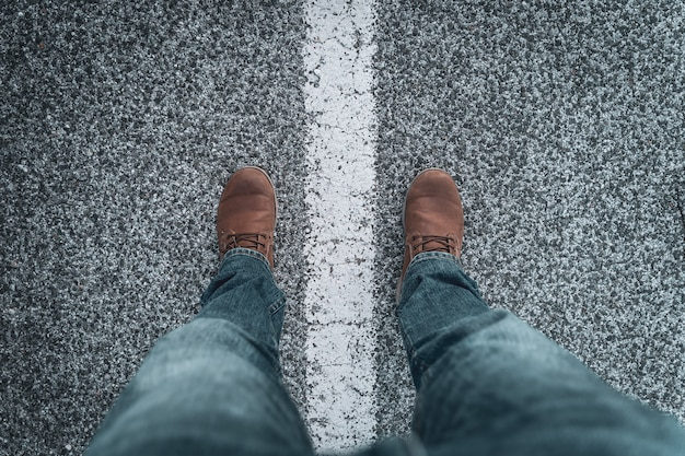 Botas e pernas masculinas na estrada do outro lado da linha. conceito de exploração e aventuras.