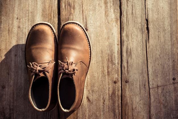 Botas elegantes marrons na madeira, cor retrô