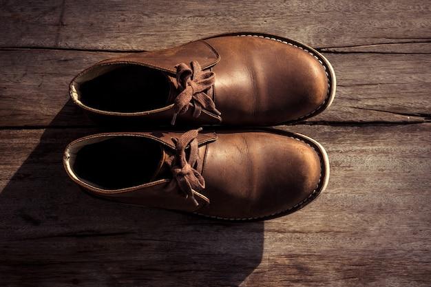 Botas elegantes marrons na madeira