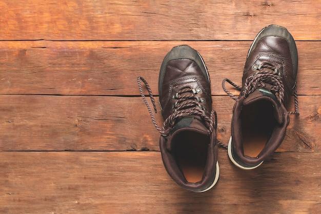 Botas em um fundo de madeira. conceito de caminhadas, turismo, acampamento, montanhas, floresta.