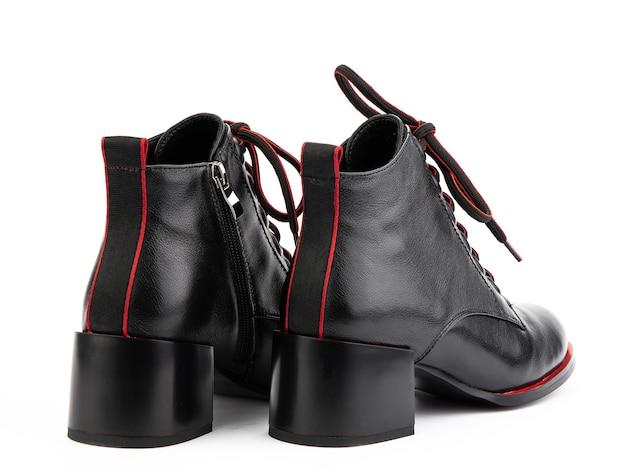Botas femininas de couro preto outonal com atacadores vermelhos e salto médio isolado branco