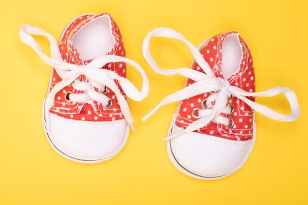 Botas infantis vermelhas com bolinhas brancas sobre amarelo