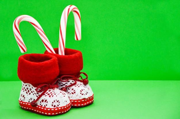 Botas infantis vermelhas e brancas de natal e bastões de doces listrados em verde brilhante