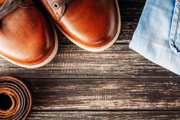 Botas masculinas de couro marrom, cinto e jeans azul sobre um fundo escuro de madeira