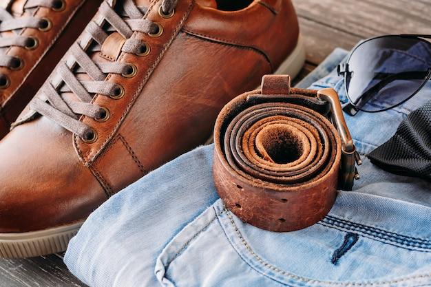 Botas masculinas de couro marrom, cinto, óculos de sol e jeans azul