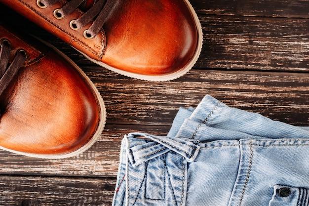 Botas masculinas de couro marrom e jeans azul sobre um fundo escuro de madeira