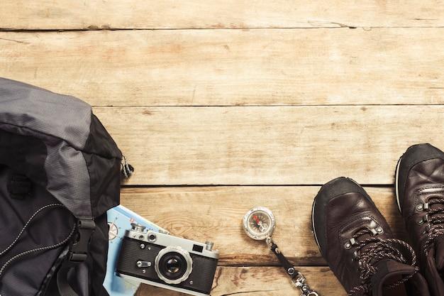 Botas, mochila, bússola e outros equipamentos de camping em uma superfície de madeira. o conceito de caminhadas nas montanhas ou na floresta, turismo, descanso de barraca, acampamento. vista plana leiga, superior.