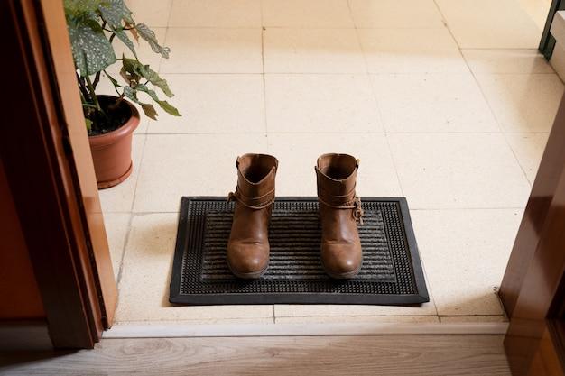 Botas na entrada da casa no capacho