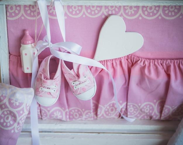 Botas para uma criança no fundo rosa