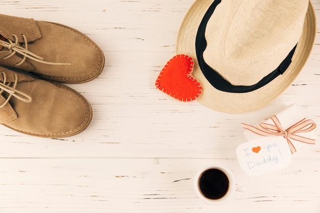 Botas perto de chapéu com coração e presente