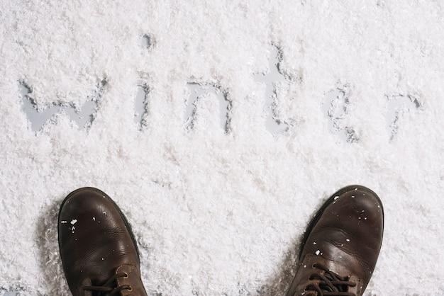 Botas perto de título de inverno na superfície de neve