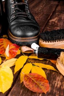 Botas pretas à prova d'água na superfície de madeira com equipamento de polimento de folhas de outono,