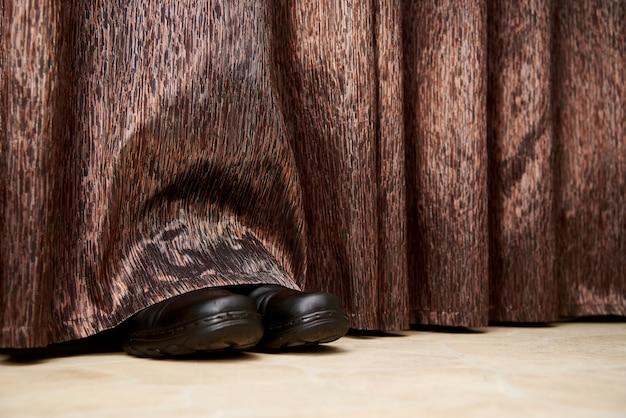 Botas saem de debaixo das cortinas.