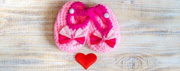 Botinhas de bebê e coração em um fundo claro