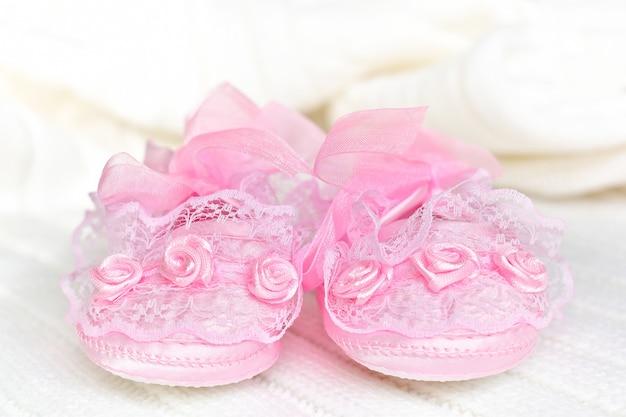 Botinhas de bebê rosa na frente, sobre manta de crochê branca.