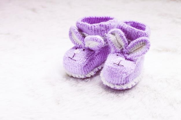 Botinhas de bebê roxas tricotadas com focinho de coelho sobre pele