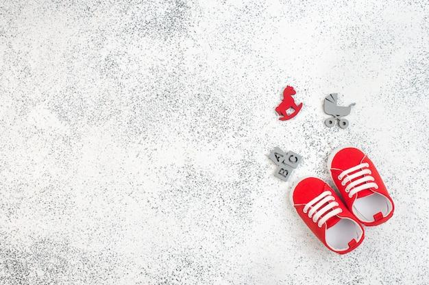 Botinhas de bebê vermelhas e acessórios de bebê em branco