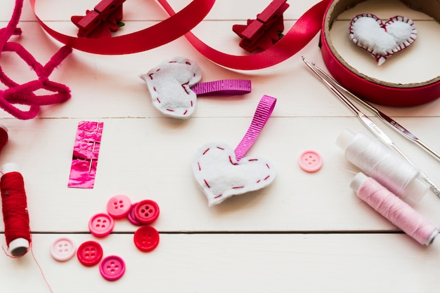 Botões; agulhas de crochet; bobinas de fio; fitas para costura forma de coração de tecido na mesa de madeira