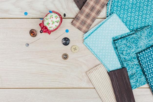 Botões; almofada de alfinetes de feltro artesanal e tecido dobrado azul na mesa de madeira