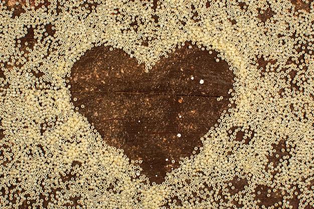 Botões amarelos em torno da forma do coração em um piso marrom rústico de madeira