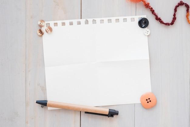 Botões; caneta em branco papel em branco sobre a mesa de madeira