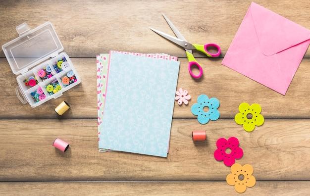 Botões; carretel e papel colorido com tesoura na mesa de madeira