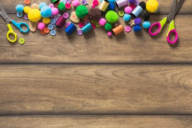 Botões coloridos; carretel; tesoura e bolas de algodão na mesa de madeira com espaço para texto