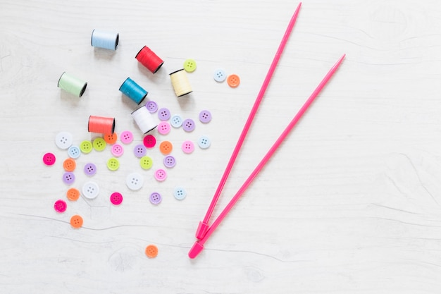 Botões coloridos e carretel com agulhas de malha rosa no pano de fundo texturizado branco