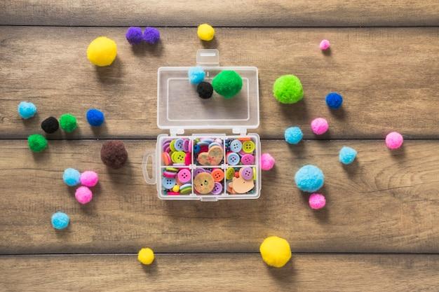 Botões coloridos em uma caixa branca aberta com bolas de algodão no pano de fundo de madeira