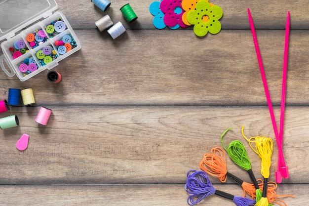 Botões coloridos na caixa com carretel; agulhas de malha e fio de fio dental na mesa de madeira