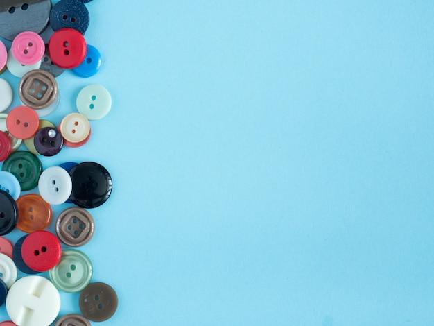 Botões coloridos no fundo azul com a embreagem lisa do espaço da cópia.