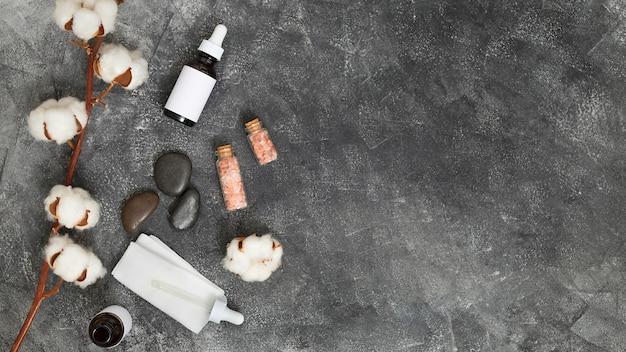 Botões de algodão no galho; garrafas de óleo essencial; último; papel de seda e sal-gema do himalaia em pano de fundo preto concreto