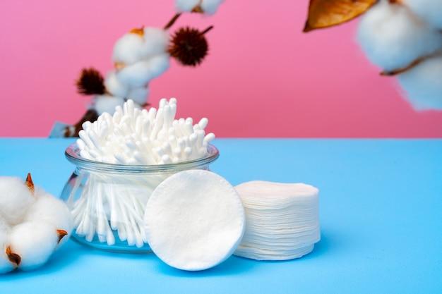 Botões de algodão para limpar orelhas em fundo rosa e azul