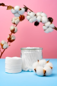 Botões de algodão para limpar orelhas em superfícies rosa e azul