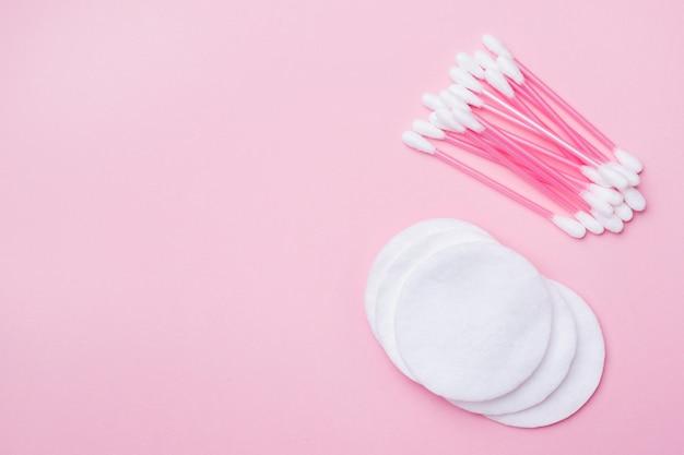 Botões de algodão rosa e cotonetes em rosa. fundo com copyspace
