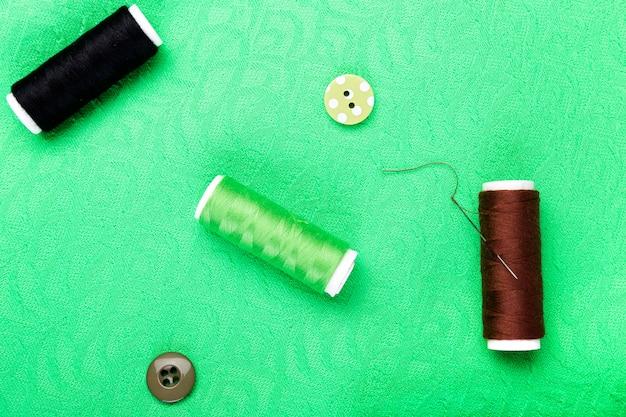 Botões de costura, carretéis de linha e pano na mesa de madeira