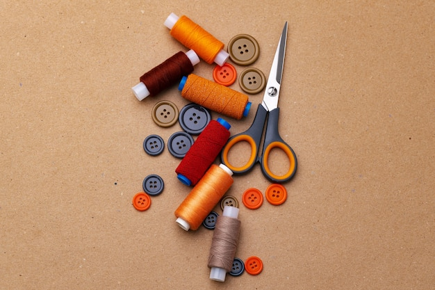Botões de costura e tesouras em fundo bege