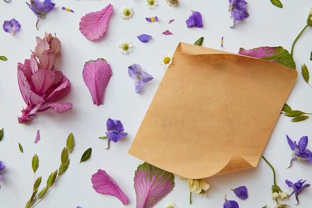 Botões de flores coloridas em um fundo branco com um pedaço de papel kraft para texto, camada plana