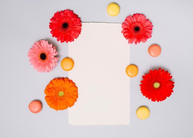 Botões de flores com biscoitos e papel na mesa